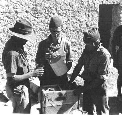 photo showing WWII british troops pouring out rum from a demijohn marked S.R.D