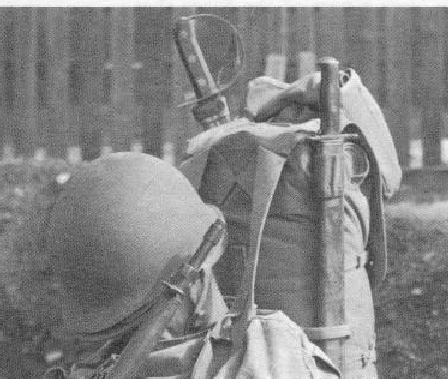 closeup of rucksack showing stored bayonet in front and M1941 Klewang in rear of Ruck Sack